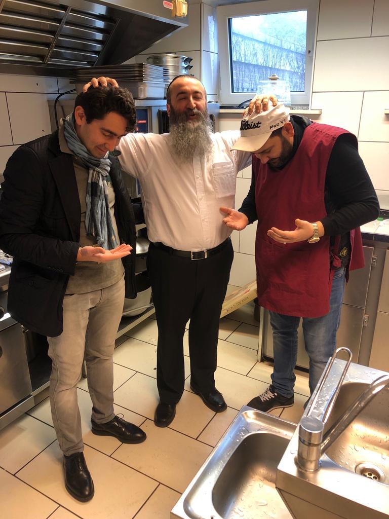 Р. Гилель Хаимов дает браху - благословение двум молодым бухарским евреям. Их сложенные ковшичком ладони означают, что они «берут» благословение, как будто бы это был осязаемый предмет.